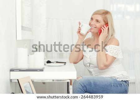 Entertaining with phone calls to friends. Attractive blond woman laughing and drinking coffee while sitting at home near the mirror
