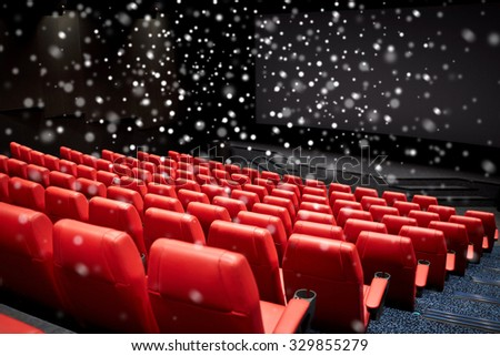 entertainment and leisure concept - movie theater or cinema empty auditorium with red seats over snowflakes - stock photo