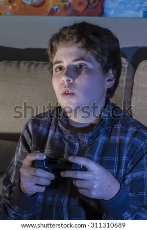 Entertainment. boy with joystick playing computer game at home.