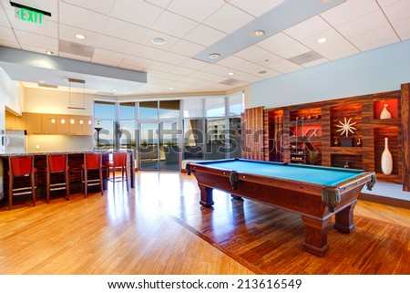 Entertainment room with pool table and walkout deck in residential building - stock photo