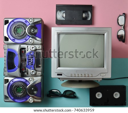 Entertainment 80s. Retro media technologies. Black white lamp TV, tape recorder, video cassette, 3d glasses on a blue pink pastel background. Top view. Flat lay.