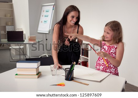 Enthusiastic attractive young girl in art class with her teacher or mother pointing her hand and smiling, interior portrait in a classroom or office