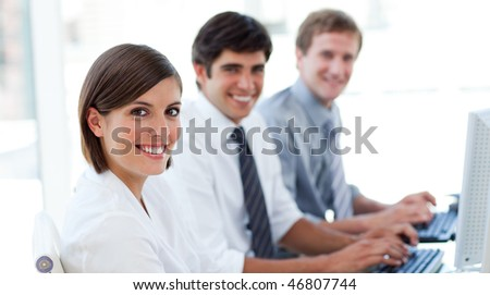 Enthusiastic business people working at computers in the office - stock photo