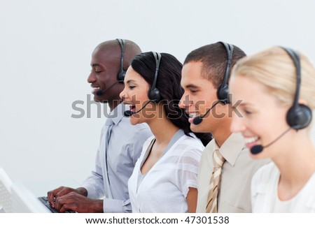 Enthusiastic business people working in a call center in the office