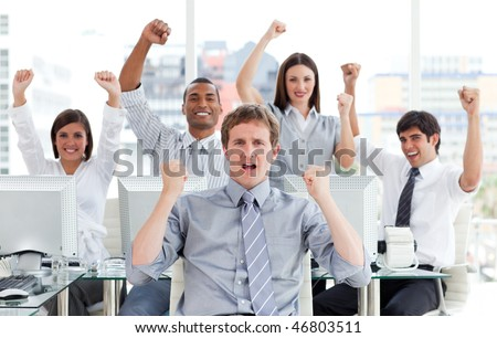 Enthusiastic business team celebrating success in the office - stock photo