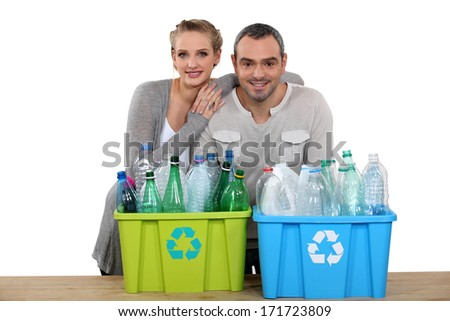 Enthusiastic couple recycling - stock photo