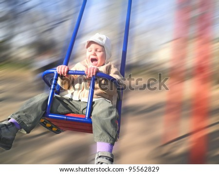 Enthusiastic kid on a swing - stock photo