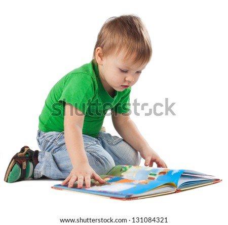Enthusiastic little boy with a book sitting on the floor, isolated on white - stock photo