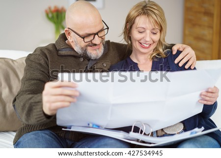 Enthusiastic loving middle-aged couple planning a new house sitting arm in arm on a sofa at home looking at a blueprint - stock photo