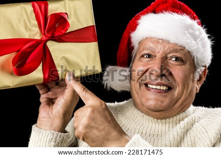 Enthusiastic male senior is pointing his left index finger at a golden wrapped gift held at eye-level in his right hand. Eyes and mouth open. Red bow and Santa Claus cap. Reminder for gift giving. - stock photo