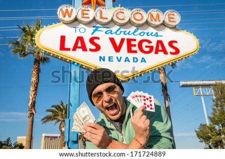 Enthusiastic man with dollars and royal flush in front of Las Vegas sign - stock photo