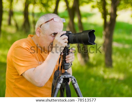 Enthusiastic mature photographer taking professional photo outdoor. - stock photo
