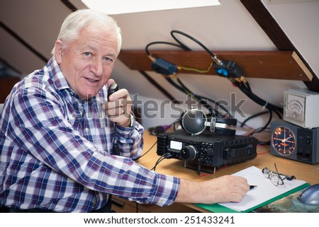 Enthusiastic middle-aged radio-amateur at his station - stock photo