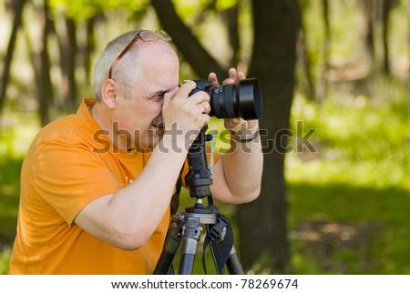 Enthusiastic photographer taking a photo outdoor. - stock photo