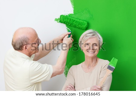 Enthusiastic senior couple renovating their home painting the wall with a bright green paint with the wife giving the camera a beaming smile - stock photo