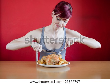 Enthusiastic skinny young woman about to eat a whole chicken - stock photo