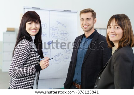 Enthusiastic successful young business team working on a project with focus to a friendly smiling young woman or team leader as they stand in front of a flip chart - stock photo