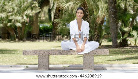 Enthusiastic woman sitting on granite bench - stock photo