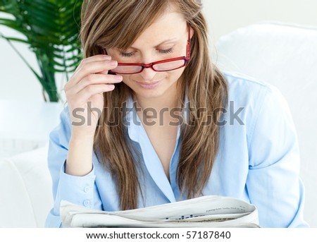 Enthusiastic woman with red glasses reading a newspaper at home