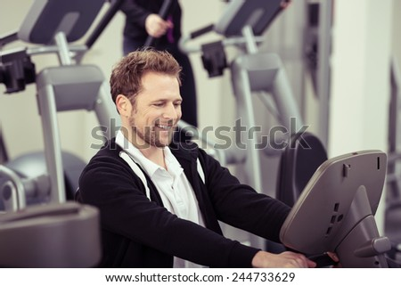 Enthusiastic young man working out in a gym smiling happily as he watches the digital readout on the monitor showing his performance - stock photo