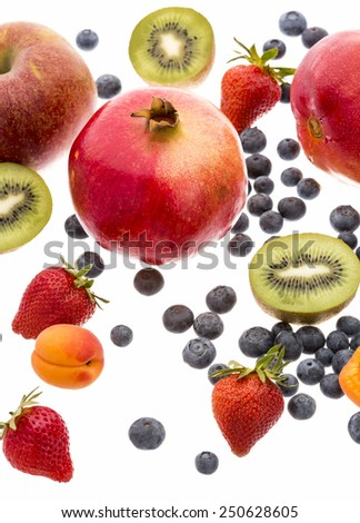 Entire pomegranate amidst a variety of fruit isolated on white background. Apricot, strawberry, kiwi fruit, apple, mango and plenty of blueberries. Studio shot. Close-up. Cutout. Wide depth of field. - stock photo
