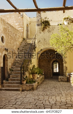 entrance and stair of Arkadi monastery courtyard, Crete, Greece - grain added in purpose to give an aged moody effect to the image