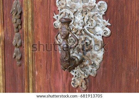 entrance door and ornaments of romantic catholic church in south germany historical city with red orange colors and silver plating ironwork handicraft