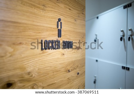 Entrance door to a men locker room in the gym.Spa,swimming pool,gym locker room door with caption sign and little grey lockers in the background.Sportsmen locker room.Sport changing room - stock photo