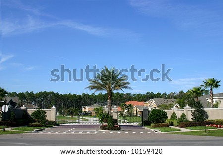 Entrance gate to a gated community in Central Florida, USA. Palm tree centered in shot with homes visible behind the wall and gate.