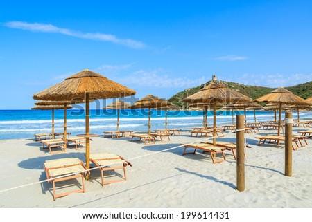 Entrance gate to white sand beach with sunchairs and umbrellas in Porto Giunco bay, Sardinia island, Italy  - stock photo