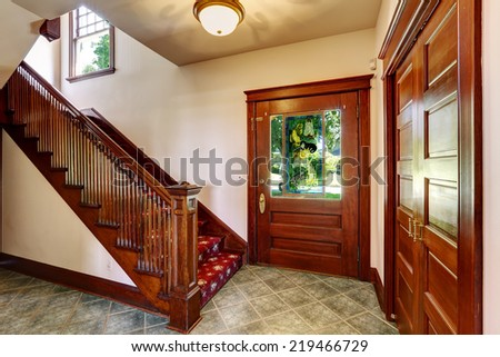 Entrance hallway with wooden staircase and red carpet covered steps - stock photo
