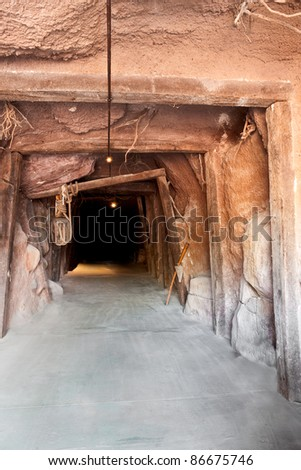 Entrance into the darkness of a mine. - stock photo