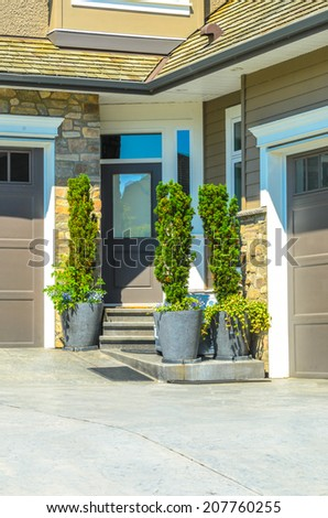 Entrance of a house decorated with some plants in the pots. - stock photo