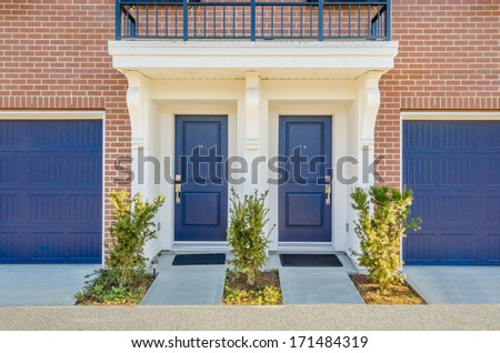 Entrance of a house. Double door with two garage doors. - stock photo