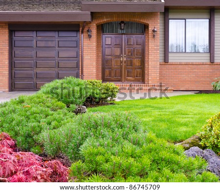 Entrance of a house with garage door and window over beautiful outdoor landscape - stock photo