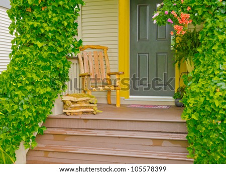 Entrance of a house with the hand made wooden chair on the porch and ivy on the rails - stock photo