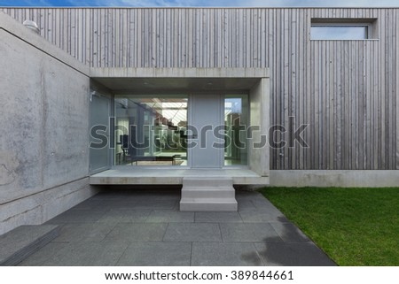 Entrance of a modern house in concrete and wood, exterior - stock photo