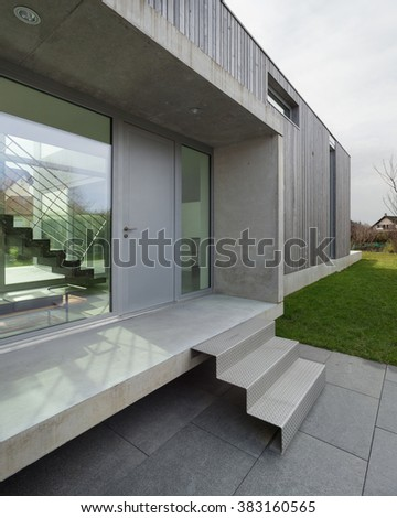 Entrance of a modern house in concrete and wood, outside - stock photo