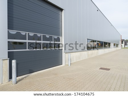 entrance of a modern warehouse with roller door - stock photo