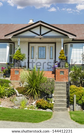 Entrance of a nice house with outdoor landscaping and blue sky background - stock photo