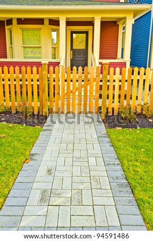 Entrance of a nice house with path and wooden fence - stock photo