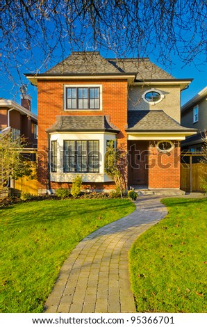 Entrance of a red brick house with path over blue sky - stock photo