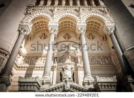 Entrance of basilica of Notre Dame de Fourviere, Lyon, France, Europe. Grand facade of historical building with high columns and arches, statues and relief patterns. Architecture of Europe. - stock photo
