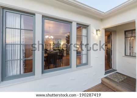 Entrance of beautiful villa, looking through windows from outside to inside at twilight. - stock photo