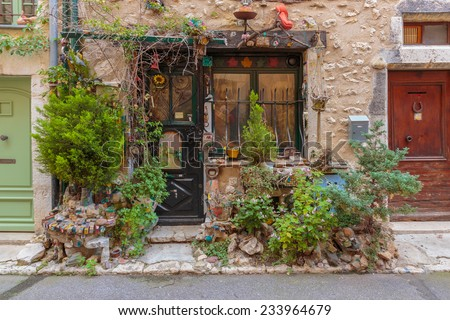 Entrance of the old village house decorated with flowers and old things, Provence France - stock photo