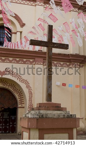 Entrance of the Temple of San Francisco in San Cristobal de las Casas Chiapas, showing the cross and the flags in front - stock photo