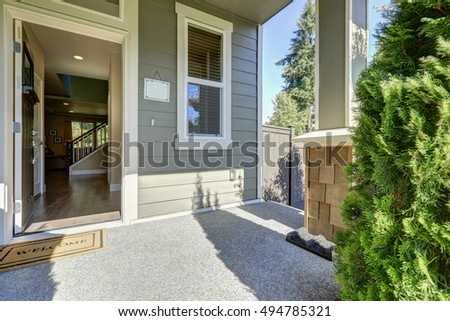 open front door. entrance porch of american gray house with open front door welcome mat on a sunny