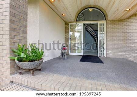 Entrance porch with glass door. Porch decorated with statue and large stone flower pot - stock photo