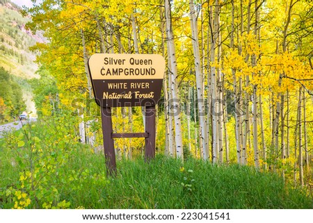 entrance sign to Silver Queen campground in Colorado amidst colorful aspens of autumn - stock photo