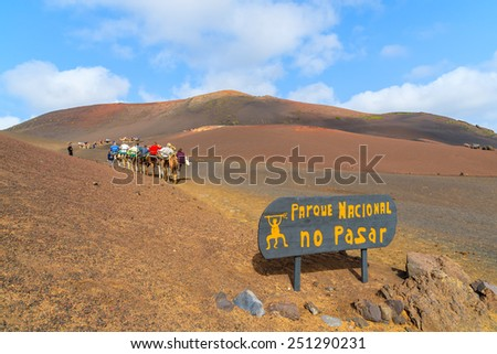 Entrance sign to Timanfaya National Park with caravan of camels in distance, Lanzarote, Canary Islands, Spain - stock photo